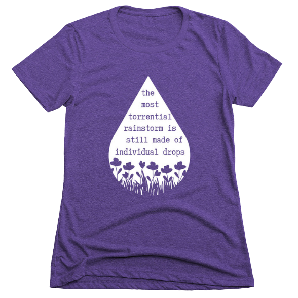 """Purple t-shirt showing a graphic of a raindrop and flowers growing. Text says """"the most torrential rainstorm is still made of individual drops."""